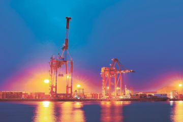 夕闇迫る高砂埠頭(ふとう)。まばゆい光に包まれたガントリークレーンがコンテナの積み下ろし作業に当たる