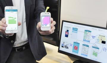 スマートフォンに表示される、シャープとセコムが連携し提供する高齢者見守りサービスのデモ画面。右下はサービスのイメージを表示するモニター=24日、東京都内