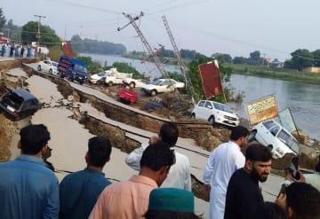 地震で陥没した道路付近に集まる人たち=24日、パキスタン・ミルプール(ロイター=共同)