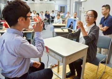 運用方法を説明したデモンストレーション。タブレット端末を通して手話でのやりとりを可能にする=川崎市中原区