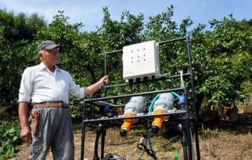 松岡さんと、水や肥料を農園にまく装置。適量をAIが自動で判断する