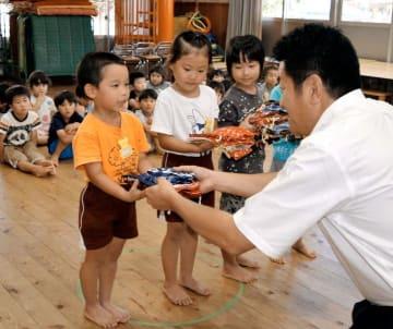 岡原市長(右)から巾着袋を受け取る園児代表