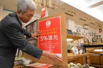 キャッシュレス決済のポイント還元制度のポスターを店内に貼る長谷川社長=24日午後、宇都宮市曲師町の長谷川時計店
