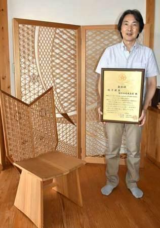 クールジャパンアワードを受賞した猪俣美術建具店の猪俣一博さんと、組子の椅子とついたて=上越市