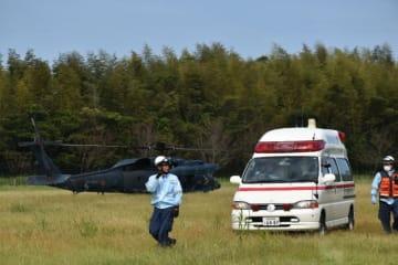 空自ヘリから要救助者を引き受け、搬送する東児湯消防組合の救急隊員ら=25日午後、高鍋町南高鍋・宮崎キヤノングラウンド