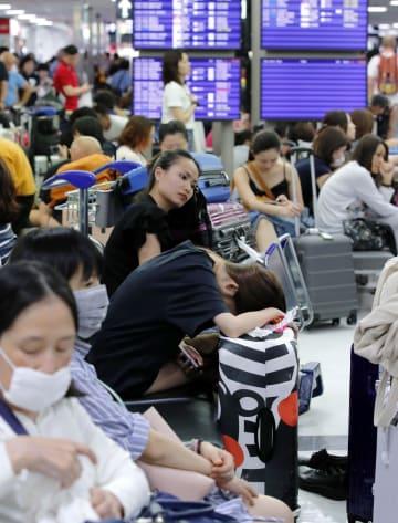 台風15号の影響で主要交通機関が長時間運休し、疲れた様子で座り込む成田空港の利用客=9日夜