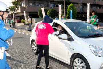 横断歩道での一時停止などを呼び掛ける交通茶屋の参加者=25日午後、松山市須賀町