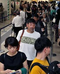 手荷物検査が再開され、保安検査場に進む下柳剛さん=26日午後、大阪(伊丹)空港(撮影・風斗雅博)