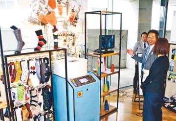 大手アパレル担当者らに、多品種少量生産に対応できる「高岡LAB(ラボ)」の取り組みを紹介する展示=東京・南青山