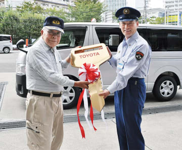 寄贈した車両の前で笑顔の中田さん(左)