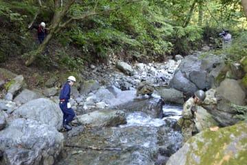近くの小川で行方不明となっている小倉美咲さんを捜索する消防隊員や自衛隊員ら=27日午前、山梨県道志村