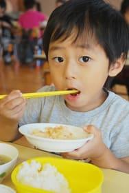 アイヌの伝統料理を口に運ぶ男の子=はまなす保育園