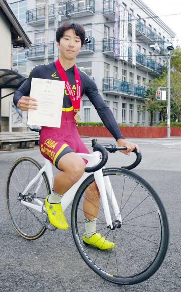 全国優勝のメダルと賞状を手に競技用自転車にまたがる中村さん=東金市