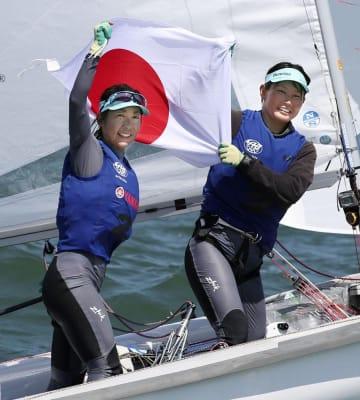 セーリングの世界選手権女子470級で2位となり、日の丸を掲げ喜ぶ吉田愛(左)、吉岡美帆組=2019年8月9日、神奈川県江の島ヨットハーバー沖