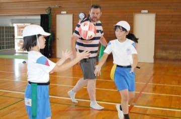 コーチに教わりながらボールをパスする児童
