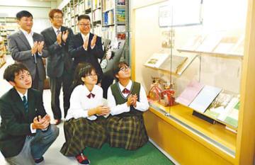 同窓会コーナー棚の設置を祝う山崎同窓会長(後列右)や生徒ら
