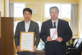 感謝状を手にする北海道キリンビバレッジの渡辺本部長(左)と目録を持つ早来中の木村校長