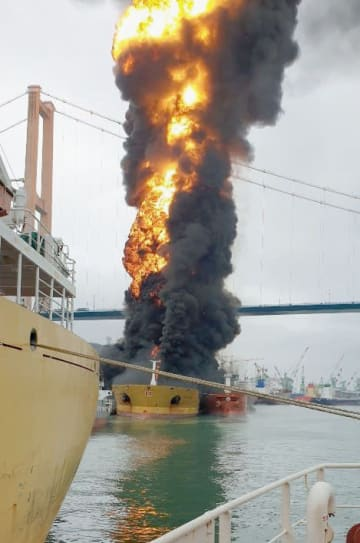 爆発が起きて炎上するタンカー(奥)=28日、韓国・蔚山(聯合=共同)