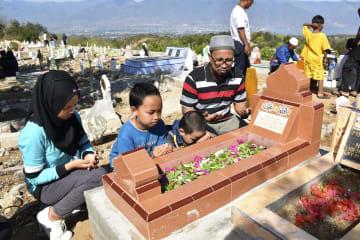 町を見下ろす集団墓地で、亡くなった妻への祈りをささげるアブドゥル・ガフルさん(左から4人目)と子どもたち=28日、インドネシア・パル(共同)