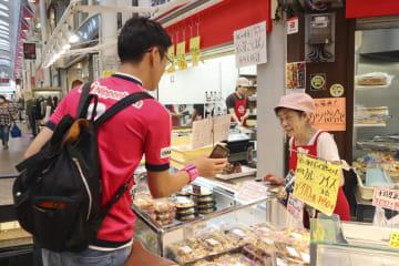 セレッソ大阪の実証実験に参加し、商店街に立ち寄ったサポーター=28日、大阪市
