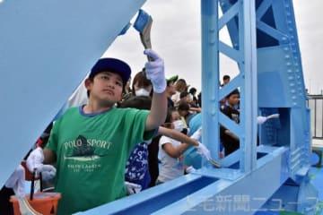 戦争遺構でもある旧橋のモニュメントを塗装する子どもたち
