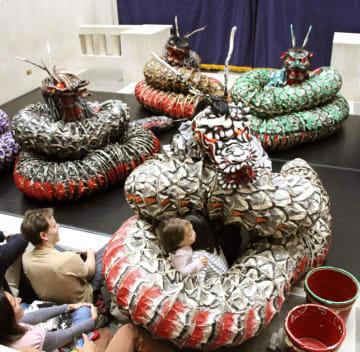 ロンドンで披露された石見神楽の演目「大蛇」で、客席の子どもに巻き付く大蛇=28日(共同)