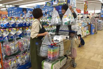 ホームセンターで洗濯洗剤などをまとめ買いする夫婦ら=28日午前、ひたちなか市新光町