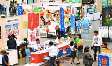 住宅情報の展示ブースを見て回る来場者=徳島市のアスティとくしま