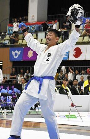 空手成年男子個人組手重量級で初優勝を飾り、両手を突き上げる熊本の飯村吏毅哉(綱田牧場)=牛久市運動公園体育館
