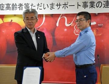 協定書にサインした後、がっちりと握手する青山署長(右)と桜田市長