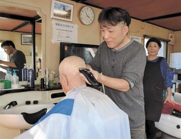 プレハブ仮設店舗で髪を切る光男さんと見守るみつさん