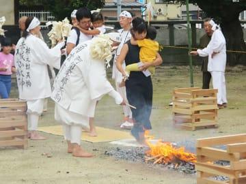 子どもを抱えて火床の上をはだしで渡る家族連れ=28日午後、加須市不動岡の不動ケ岡不動尊總願寺