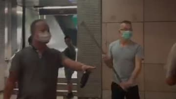 One man wields a pipe while attacking people near the Fortress Hill Lennon Wall. Photo: screenshot.