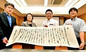 豊臣秀吉が島津氏に宛てた「刀狩令」のレプリカを持つ東京大学史料編纂所の本郷恵子教授(左から2人目)ら=都城島津邸