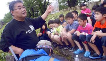 子どもたちに川で淡水魚について教える鈴木康之さん(左)=2017年、酒田市(遺族提供)
