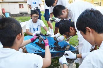前年度、ろ過装置に使われた使い捨てカイロの中身を取り出し、プランター用の土に再利用する生徒たち=佐賀市鍋島の鍋島中