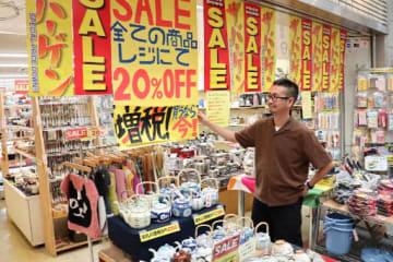 店頭に張り紙をして、買い物客にアピールする山本社長=大阪市旭区の千林商店街
