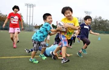 楽しそうにラグビーをプレーする子どもたち=28日、新潟市中央区