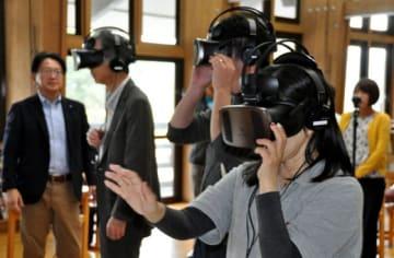 VR動画を視聴し、石碑周辺の状況を仮想体験する参加者