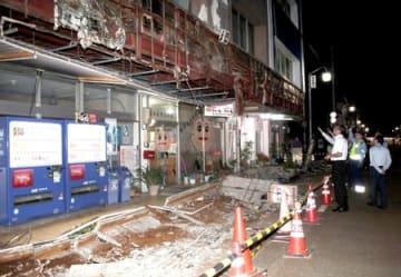 外壁の一部が崩落したビル。破片が路上に散乱していた=30日、新潟市秋葉区新津本町3