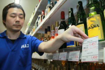 酒類の消費税は8%から10%に。大分市府内町の酒店「オーリック府内町店」では、税率8%の値札の下に新税率に対応した値札を入れて準備した=30日午後9時44分
