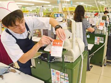 1日から始まるキャッシュレス決済のポイント還元を伝えるポップをレジに貼る担当者=30日午後4時37分、スーパー三心鏡島店