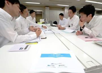 打ち合わせをする十八銀行員(右側)と親和銀行員=長崎市、十八銀本店