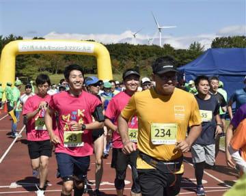 風力発電施設を望む陸上競技場からスタートする選手たち
