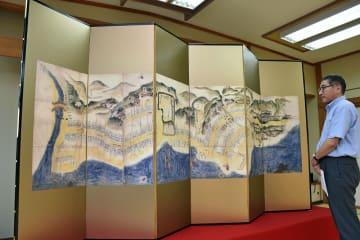 江戸時代に描かれた町絵図を基に制作された「鯵ケ沢屏風」に見入る平田町長