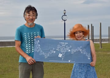 「C-POINT」の会場で第10回開催時に制作した手ぬぐいをかかげる安田さん夫妻=鯵ケ沢町の新設海浜公園
