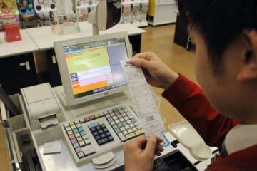 レシートに軽減税率が正しく反映されているかチェックする店員=1日午前4時45分、ハローズ中庄店