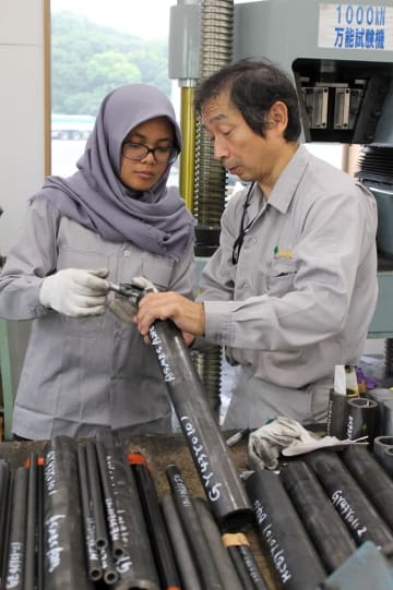社員(右)の説明を受けながらパイプの厚みを計測するナビラさん=佐世保市、大阪鋼管