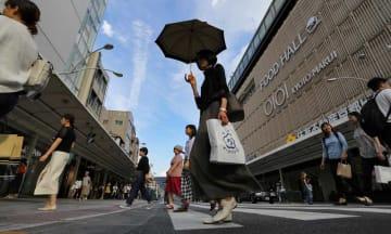 真夏を思わせる日差しを日傘でしのぐ女性ら(1日午後2時53分、京都市下京区四条通河原町)