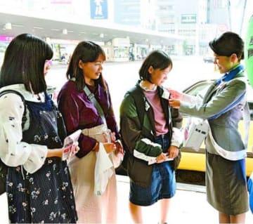 募金に協力し、赤い羽根を付けてもらう人=徳島駅前
